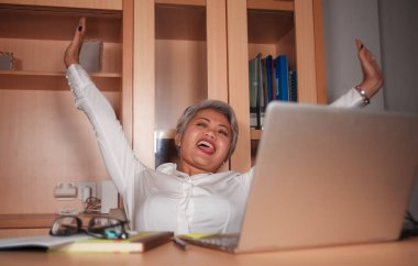 Happy and successful attractive middle aged Asian woman working at office laptop computer desk excited and cheerful celebrating business victory laughing