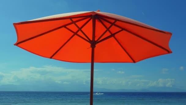 Orangefarbener Sonnenschirm vom Wind am Strand des tropischen Paradieses vor blauem Meer im Inselferien- und Reisezielkonzept