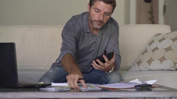 giovane uomo attraente e occupato in soggiorno divano divano contabilità spese mensili e pagamenti del debito utilizzando calcolatrice conteggio reddito finanziario nazionale e documenti fiscali presso appartamento moderno