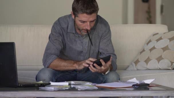 junger attraktiver und beschäftigter Mann auf dem Sofa im Wohnzimmer, der monatliche Ausgaben und Schuldenzahlungen mit einem Taschenrechner abrechnet, der Einkommen und Steuerunterlagen in einer modernen Wohnung zählt