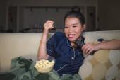 fiatal gyönyörű boldog és nyugodt ázsiai kínai nő otthon nappaliban ülve hangulatos kanapé kanapén tévénézés epizód vagy romantikus vígjáték film étkezési pattogatott kukorica