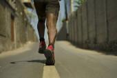 Fotografie Pohled na detail atletického černého afroamerického profesionálního sportu muži a nohy v běžících botách venku na asfaltové silnici při drsném joggingu