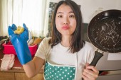 Photo domestic chores lifestyle portrait of young tired and stressed Asian Korean woman in cook apron washing dishes at kitchen sink working lazy in moody and upset face doing housework