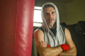 sport fitness lifestyle portrait of young happy and sweaty man boxing at gym working out sweaty in hoodie vest training on heavy bag looking coo