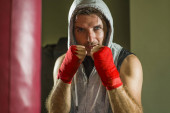 sport fitness lifestyle portrait of young happy and sweaty man boxing at gym working out sweaty in hoodie vest training on heavy bag looking cool and badass