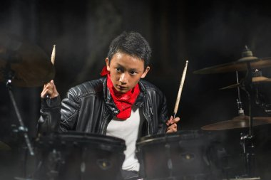 13 or 14 years old cool and talented Asian American mixed ethnicity boy playing drums in leather jacket and bandana  practicing and performing song