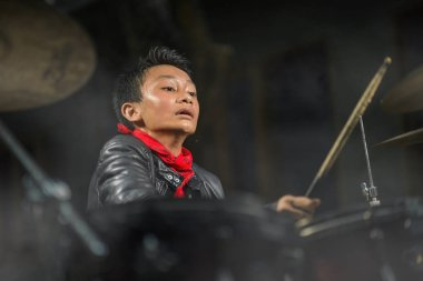 Teenager rock band musician . 13 or 14 years old cool and talented Asian American mixed ethnicity boy playing drums in leather jacket and bandana