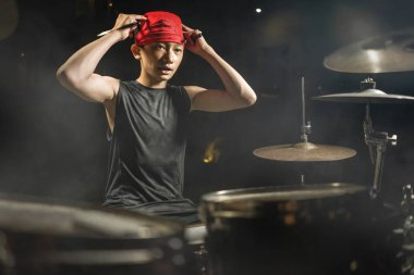 Teenager rock band musician . 13 or 14 years old cool and talented Asian American mixed ethnicity young boy playing drums adjusting headband