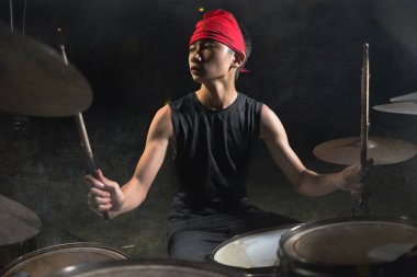 cool and talented Asian American mixed ethnicity young boy playing drums in headband practicing and performing song in dark foggy stage