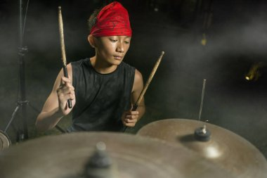 Teenager rock band drummer . cool and talented Asian American mixed ethnicity teenage boy playing drums in headband performing song in dark foggy stage