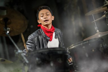 young cool and talented teenager musician playing drums on his 14 years old in leather jacket and bandana rock band style practicing and performing song on stage