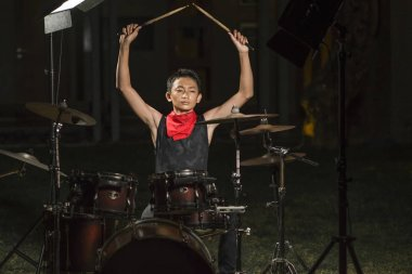 Asian American mixed teenager playing drums at home garden . cool and handsome young boy practicing on drum kit rehearsing passionate in badass rock band look