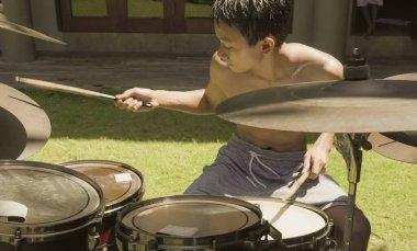 Asian American teenager playing drums. Summer portrait of handsome young boy practicing on drum kit at home garden rehearsing rock song enjoying his hobby