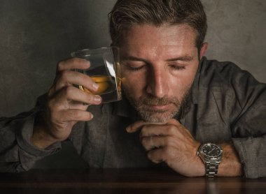 Attractive alcoholic man . depressed addict isolated in front of whiskey glass drunk and wasted in dramatic expression suffering alcoholism and alcohol addiction