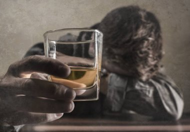 alcoholic depressed and drunk addict man sitting in front of whiskey glass trying holding on drinking in dramatic expression suffering alcoholism and alcohol addiction