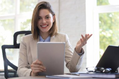 Attractive smiling woman working on a tablet in modern office