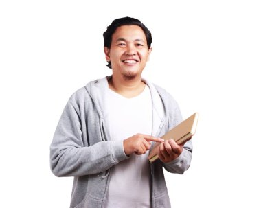 Young Asian man wearing white shirt and gray jacket holding a book, smiling expression. Isolated on white. Close up body portrait