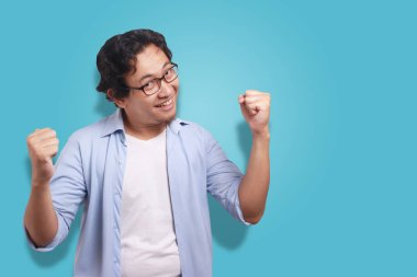 Young Asian man wearing white and blue shirt happy expression, celebrating victory gesture. Isolated on white. Close up body portrait