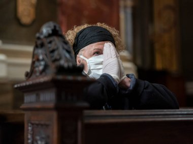 Senior woman in gloves and mask praying in a church