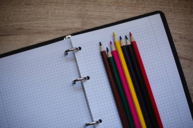 Background With Colored Pencils and Notebook On Wooden Background. Back To School Concept