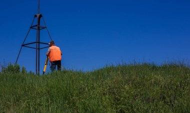 Professional Male Land Surveyor Measures Ground Control Point Using a GPS Rover. Green Field on a Backgroun