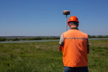 Professional Male Land Surveyor Measures Ground Control Point Using a GPS Rover. Green Field on a Background