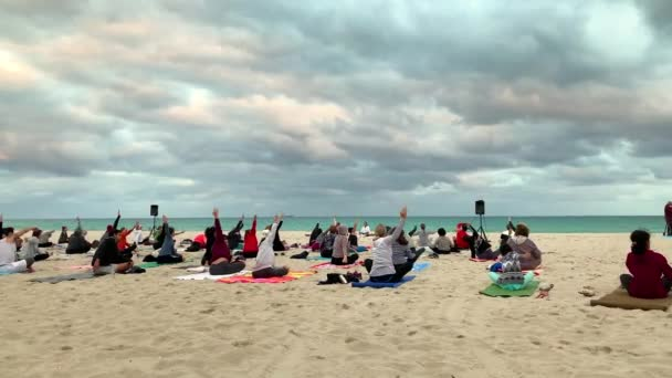 Miami, FL, USA - January 20, 2019: Group Yoga Class on the Sand Beach at Sunset. Group of People Practicing Yoga on the Beach. Full Moon in Miami