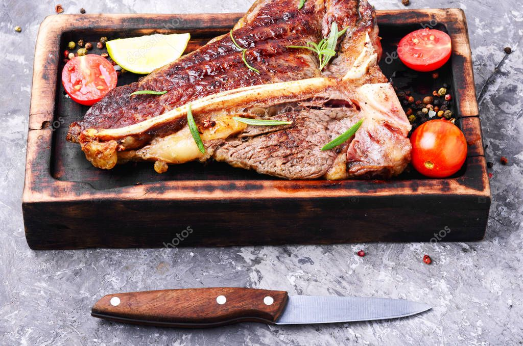 Grilled ribeye beef steak with spices on cutting board