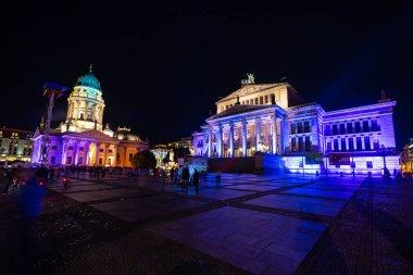 BERLIN - OCTOBER 07, 2018: Square Gendarmenmarkt, Konzerthaus (concert hall) and German Church (left) in brightly colored illuminations. Festival of lights 2018.