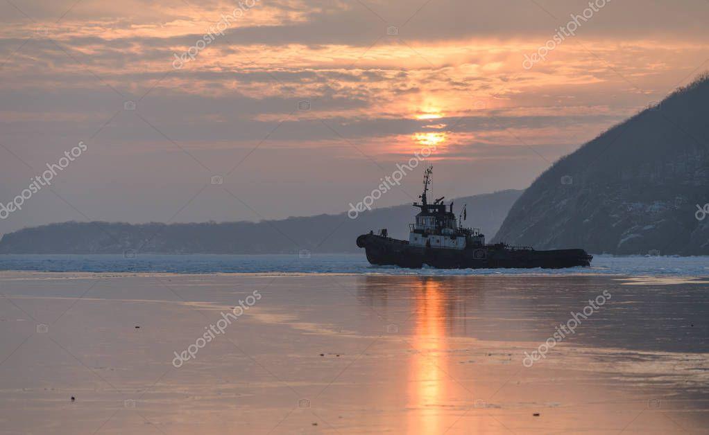 Tug boat breaking ice.