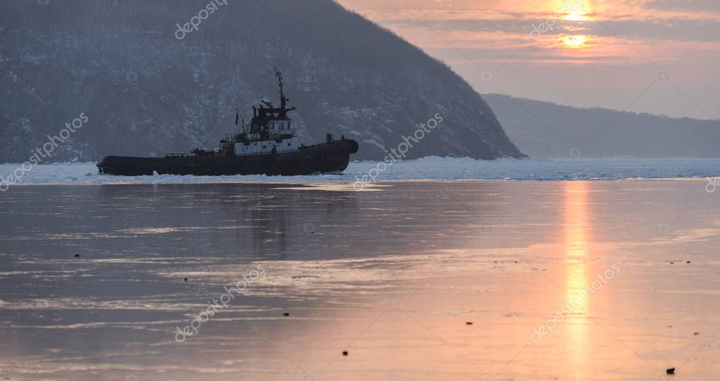 Tug boat breaking ice.