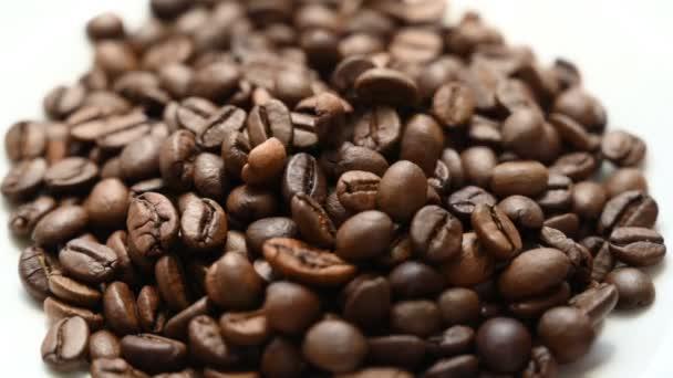 Klesající kávová zrna ve zpomaleném filmu. Selektivní fokus.