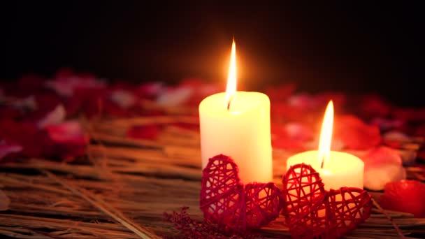 Dekoration des Filmmaterials Valentinstag mit Kerzenbrennen und Blütenblättersammlung