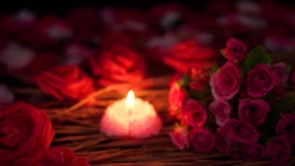 Filmaufnahmen verschwimmen von Blütenblättern, Rosenstrauß und brennenden Kerzen. Valentinstag-Kollektion