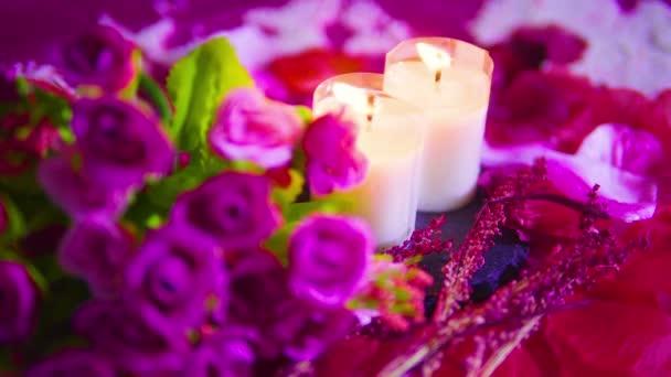 Nahaufnahmen von brennenden Rosen und Kerzen. Valentinstag-Kollektion