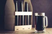 pivní lahve case a hrnek na tmavé pozadí/pivní láhve případu a hrnek na tmavém pozadí. Selektivní fokus