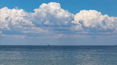 Blue sea under clouds sky with the ship on the horizon