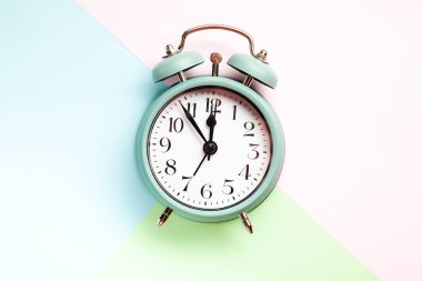 Retro style alarm clock over the pastel blue, pink and green background stock vector