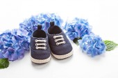 Photo Cute newborn baby boy shoes with festive decoration over the white background. Baby shower, birthday, invitation or greeting card mockup