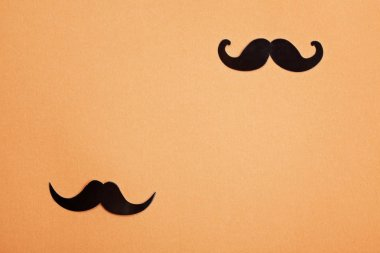 Black paper moustaches over orange background with copy space. Mens health awareness month, masculinity, fathers day concept