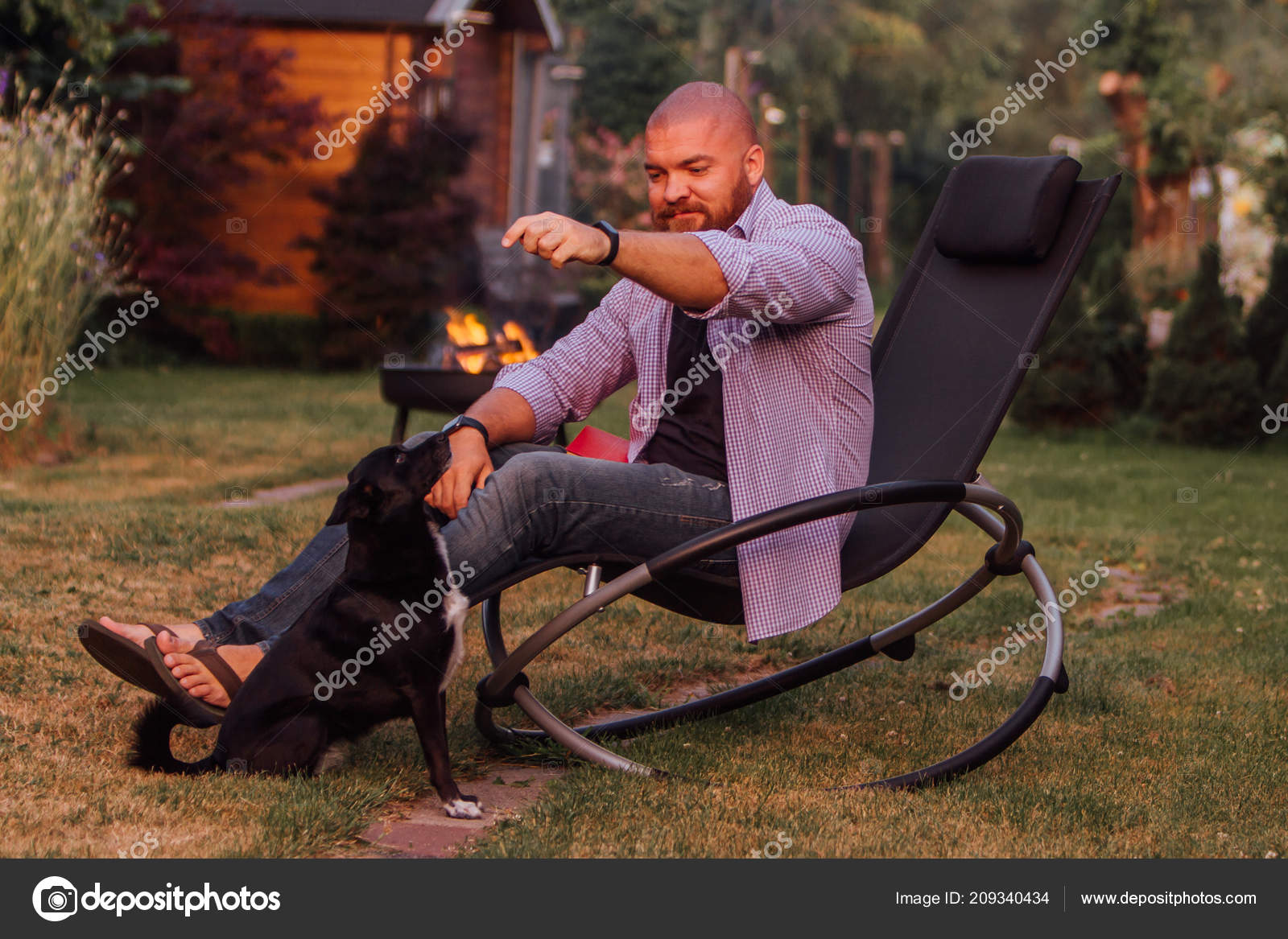 Excellent Young Man Sitting Rocking Chair Playing Little Black Dog Squirreltailoven Fun Painted Chair Ideas Images Squirreltailovenorg