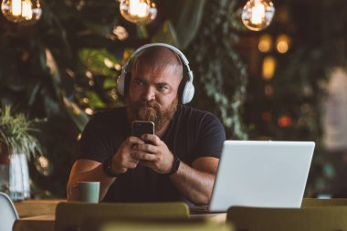 Young man with big beard is texting on the smartphone sitting in a restaurant with pc (computer - laptop) and headphones listening music or audio book