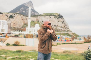 Bearded man feels cold and freezing - tourism, visiting Gibraltar, traveling concept