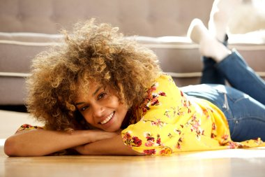 Portrait of beautiful young african american woman lying on floor at home and smiling