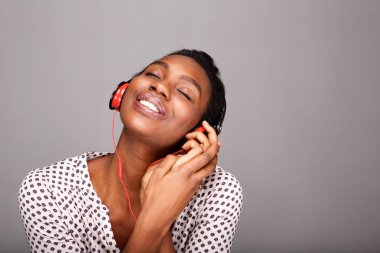 Close up portrait of happy woman listening to music on headphones with eyes closed