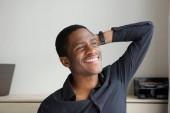 Fotografia Ritratto di giovane uomo africano felice che sorride con la mano dietro la testa
