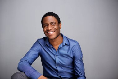 Portrait of handsome young african american businessman smiling against gray wall