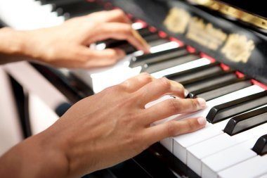 Close up female hands playing the piano