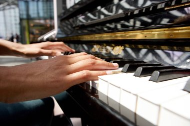 Side view young woman hands playing piano