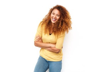 Portrait of beautiful young woman with curly hair laughing with arms crossed against white background